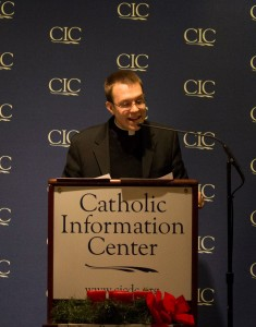Father Justin Huber speaking at the 2014 Christmas Poetry Reading.