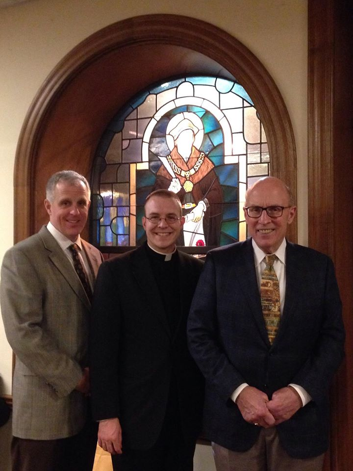 Left to right: Chris Payne, Fr. Justin Huber, and John Vittone in front of the Saint Thomas More stained glass window at the Catholic Information Center.